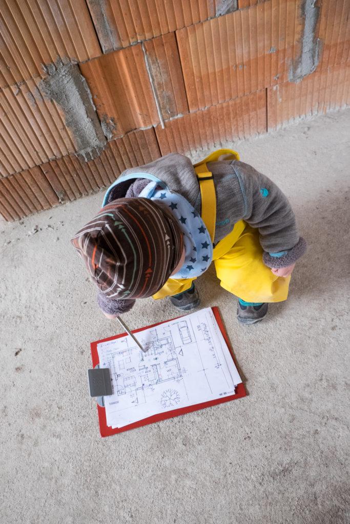 Während Bauherr und Bauherrin in Gedanken die Steckdosen platziert haben, hat der Bauleiter nochmal letzte Änderungen an den aktuellen Plänen vorgenommen.