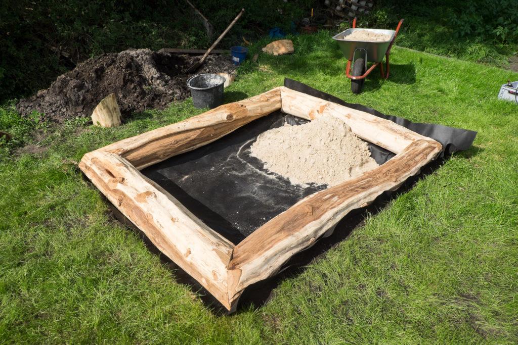 Unkrautvlies als Untergrund und die erste Schubkarre Sand